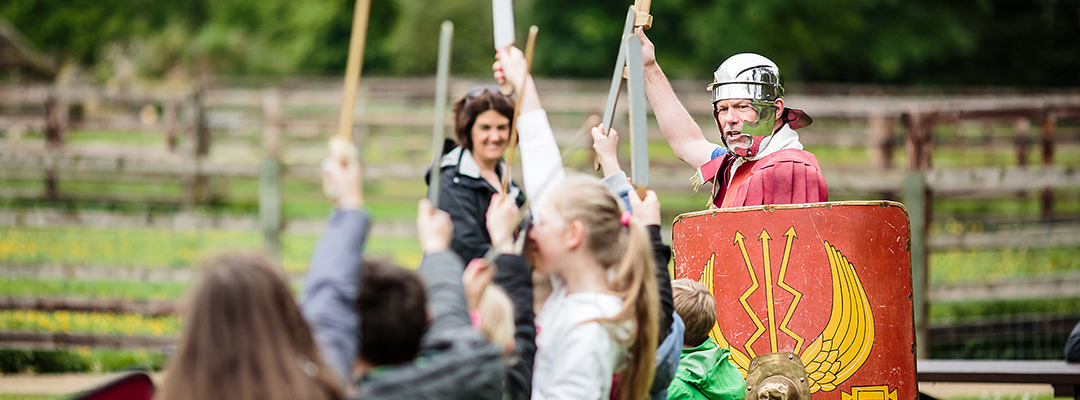 A Roman soldier holds his sword aloft, encouraging children to participate