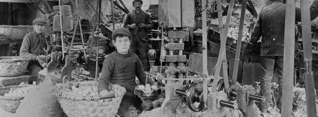 A boy working the automatic boring machine at Stott Park in about 1906